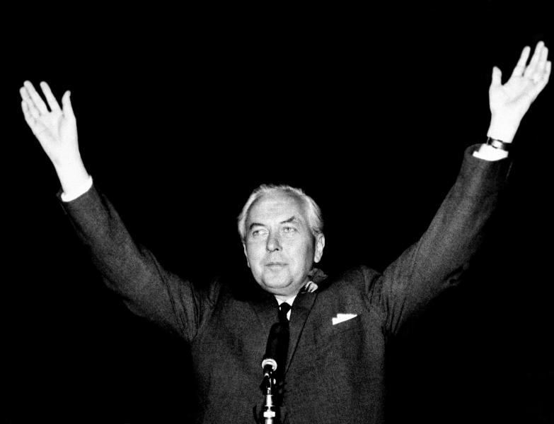 FILE - In this Oct. 15, 1964 file photo, Britain's Labour Party leader Harold Wilson raises his hands after retaining his parliamentary seat in Huyton, England and leading his party to victory. Britain is facing the most testing and significant, some would say tortuous, period in its modern history since World War II. The polarized electorate now has a critical choice to make _but it seems unlikely the result, whatever it may be, will heal deep and toxic divisions that could last a generation or more. (AP Photo, File)