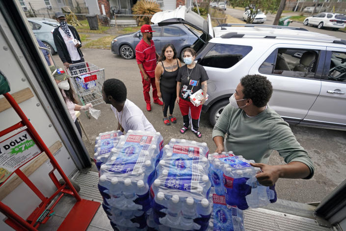 Marcel McClinton, right, hands out cases of donated water to residents affected by a severe winter storm, Friday, Feb. 26, 2021, in Houston. Local officials, including Houston Mayor Sylvester Turner, say they have focused their efforts during the different disasters on helping the underserved and under-resourced but that their work is far from complete. (AP Photo/David J. Phillip)