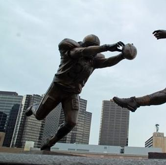 "This photo released July 27, 2012 by the New Orleans Saints shows the blocked punt that etched Steve Gleason into New Orleans Saints lore, and the symbolic significance that play took on in a city just starting to recover from disaster, is now immortalized in a nine-foot statue outside the Superdome. Gleason, who now has ALS, famously blocked the ball off of the foot of then-Atlanta punter Michael Koenen and into the end zone for a Saints touchdown on Sept. 25, 2006, the night the rebuilt Superdome and the city of New Orleans hosted an NFL game for the first time since Hurrciane Katrina. The statue, entitled ""Rebirth,"" depicts Gleason fully outstretched in a dive, his hands smothering the ball as it leaves Koenen's foot. Gleason says the statue is symbolizes the commitment of those who returned to rebuild after the storm. (AP Photo/New Orleans Saints, Alex Restrepo)"