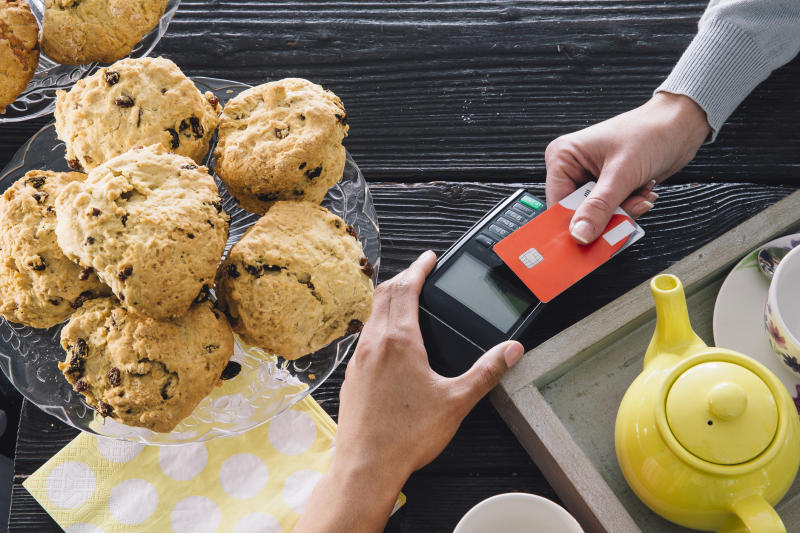 Customer reaches across table to make contactless payment with credit card as merchant's hand extends with credit card reader.