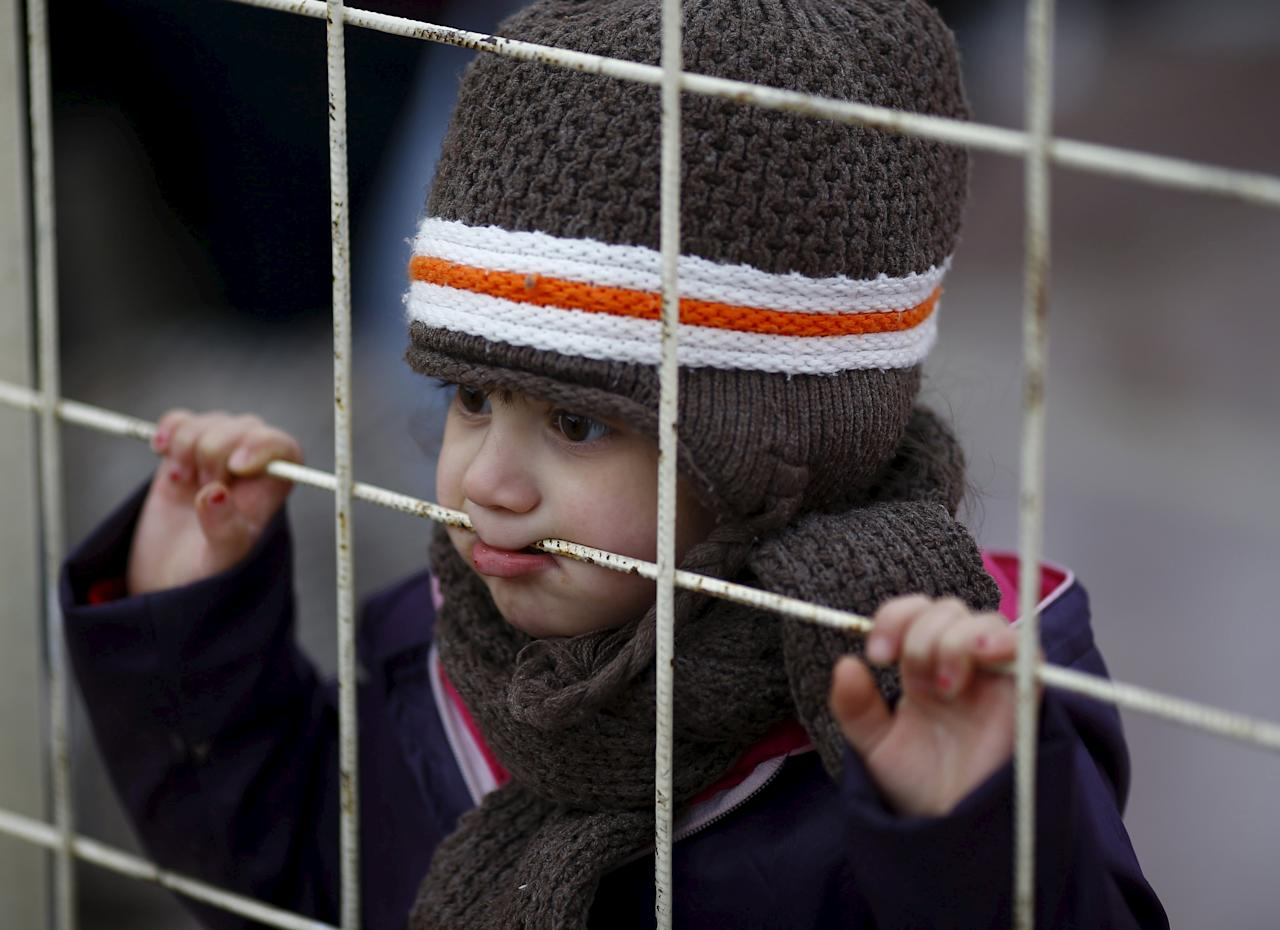A Syrian boy looks through a gate as others wait to cross into Syria at Oncupinar border crossing in the southeastern city of Kilis