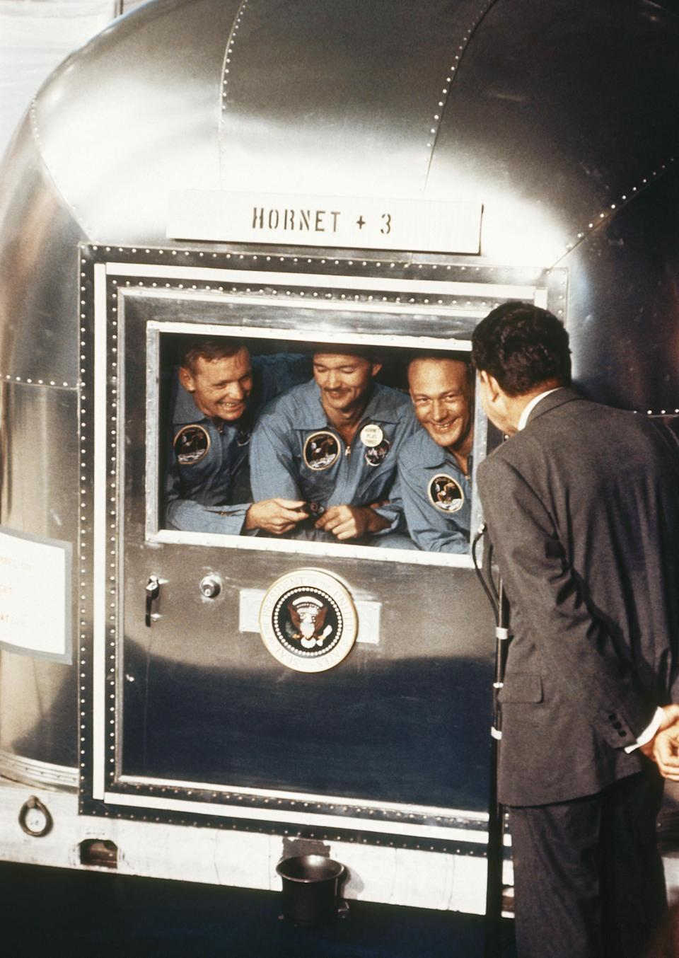 """FILE – In this July 24, 1969 file photo, President Richard Nixon, right, greets the Apollo 11 astronauts in the quarantine van on board the U.S.S. Hornet after splashdown and recovery. The Apollo 11 crew from left are Neil Armstrong, Michael Collins, and Edwin """"Buzz"""" Aldrin. (AP Photo, File)"""