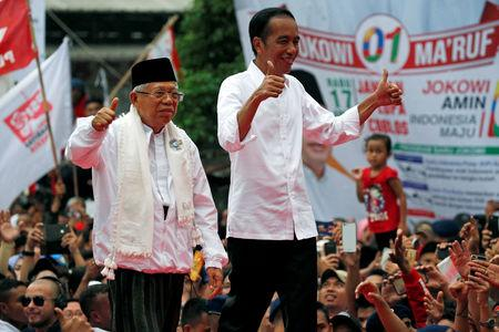 FILE PHOTO: Indonesia's incumbent presidential candidate Joko Widodo (C-R) and his running mate for the upcoming election Ma'ruf Amin (C-L) gesture as they greet their supporters at a carnaval during his campaign rally in Tangerang, Banten province, Indonesia, April 7, 2019. REUTERS/Willy Kurniawan/File Photo