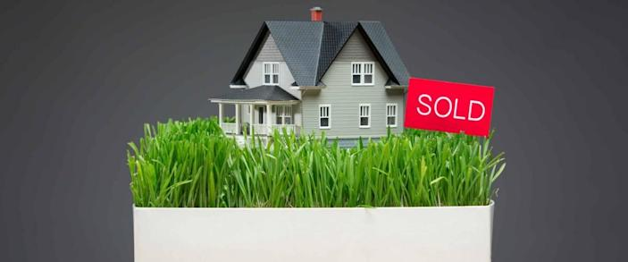 Close up of house model with green grass and sold tablet on grey background. Concept of real estate and sales