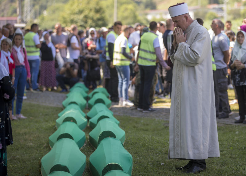 A cleric prays above coffins at the memorial cemetery in Potocari near Srebrenica, Bosnia, Thursday, July 11, 2019. The remains of the 33 victims of Srebrenica massacre will be buried 24 years after Serb troops overran the eastern Bosnian Muslim enclave of Srebrenica and executed some 8,000 Muslim men and boys, which international courts have labeled as an act of genocide. (AP Photo/Darko Bandic)