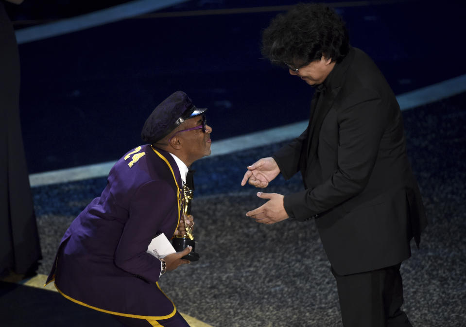 """Spike Lee, left, presents the award for best director to Bong Joon Ho for """"Parasite"""" at the Oscars on Sunday, Feb. 9, 2020, at the Dolby Theatre in Los Angeles. (AP Photo/Chris Pizzello)"""