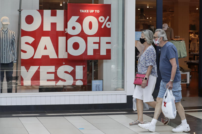 A couple walk past a store with sale signs displayed at Great Lakes Mall, Wednesday, June 10, 2020, in Mentor, Ohio. Sales for retailers has plunged since the coronavirus pandemic. (AP Photo/Tony Dejak)