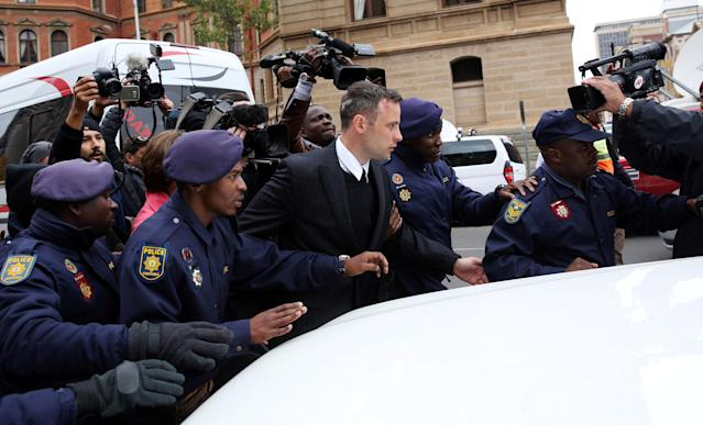 Former Paralympian Oscar Pistorius is escorted by police officers as he leaves after the second day of his sentencing for the murder of his girlfriend Reeva Steenkamp, at Pretoria High Court, South Africa June 14, 2016. REUTERS/Siphiwe Sibeko