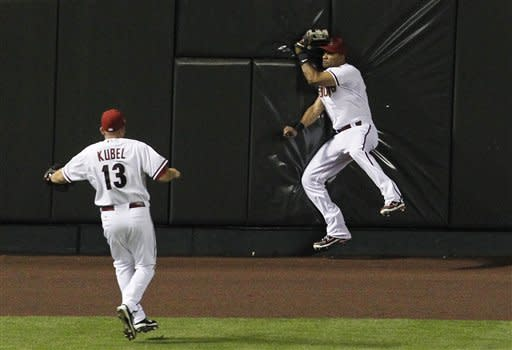 Arizona Diamondbacks' Chris Young, right, crashes into the wall while catching a fly ball hit by Pittsburgh Pirates' Pedro Alvarez as Jason Kubel (13) watches during the fourth inning of a baseball game Tuesday, April 17, 2012, in Phoenix. Young left the game after the play due to injury. (AP Photo/Ross D. Franklin)