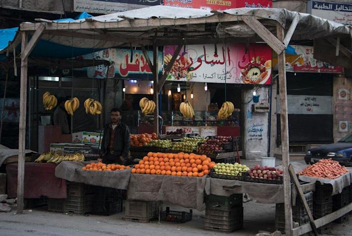 A Syrian man sells fruit and vegetables at a market in the northern embattled Syrian city of Aleppo on February 9, 2016 (AFP Photo/Karam Al-Masri)