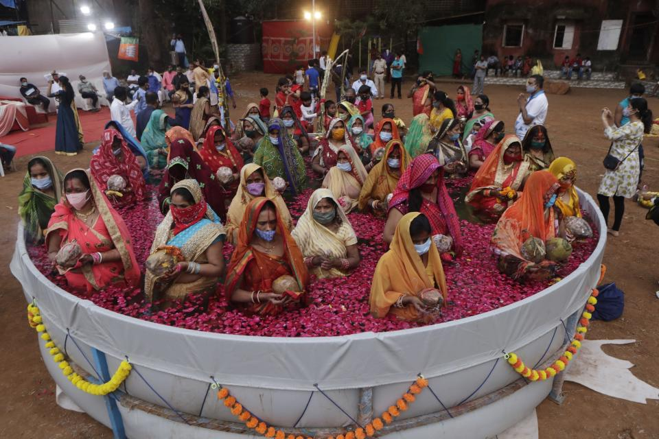 Indian women perform rituals standing inside an artificial pond on Chhat Puja festival in Mumbai, India, Friday, Nov. 20, 2020. Health officials have warned about the potential for the coronavirus to spread during the upcoming religious festival season, which is marked by huge gatherings in temples and shopping districts. (AP Photo/Rajanish Kakade)