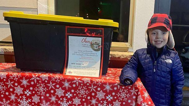 PHOTO: Hudson Galligan, 5, stands with a box for hot chocolate donations. (Lacey Galligan)