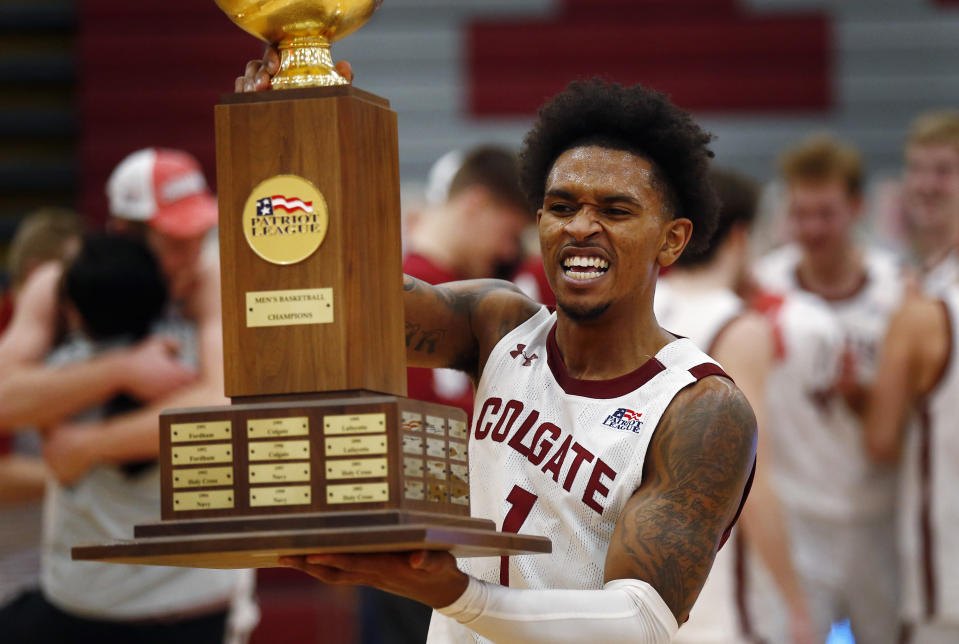 Colgate's Jordan Burns (1) celebrates with the trophy after Colgate beat Loyola (Md.) in an NCAA college basketball game in the finals of the Patriot League tournament, Sunday, March 14, 2021, in Hamilton, N.Y. (AP Photo/John Munson)