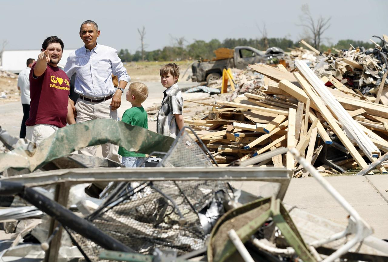 U.S. President Barack Obama talks with Daniel Smith and sons Gabriel Dority (R) and Garrison Dority as he visits the tornado devastated town of Vilonia, Arkansas May 7, 2014. The tornadoes were part of a storm system that blew through the Southern and Midwestern United States earlier this week, killing at least 35 people, including 15 in Arkansas. Obama has already declared a major disaster in Arkansas and ordered federal aid to supplement state and local recovery efforts. REUTERS/Kevin Lamarque (UNITED STATES - Tags: POLITICS DISASTER)