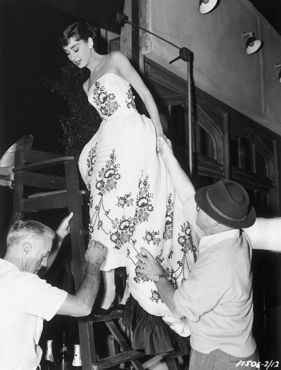 <p>Audrey Hepburn, dressed in an evening gown, is helped down a ladder by two men on the set of <em>Sabrina</em>. </p>