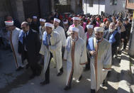 Imams lead the procession during circumcision ceremony in the village of Ribnovo, Bulgaria, Sunday, April 11, 2021. Despite the dangers associated with COVID-19 and government calls to avoid large gatherings, Hundreds of people flocked to the tiny village of Ribnovo in southwestern Bulgaria for a four-day festival of feasting, music and the ritual of circumcision which is considered by Muslims a religious duty and essential part of a man's identity. (AP Photo/Jordan Simeonov)