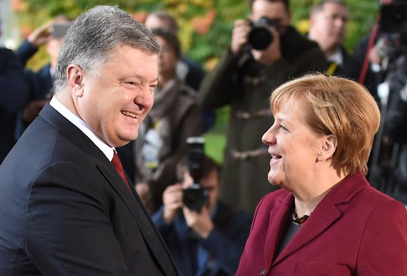 German Chancellor Angela Merkel (R) welcomes Ukrainian President Petro Poroshenko upon arrival at the chancellery on October 19, 2016 in Berlin