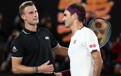 Switzerland's Roger Federer, right, is congratulated by Hungary's Marton Fucsovics after winning their fourth round singles match at the Australian Open tennis championship in Melbourne, Australia, Sunday, Jan. 26, 2020