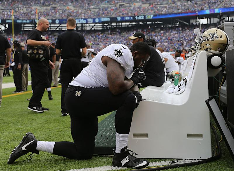 Saints defensive tackle Nick Fairley kneels on the sideline during a game against the Giants. (Getty Images)