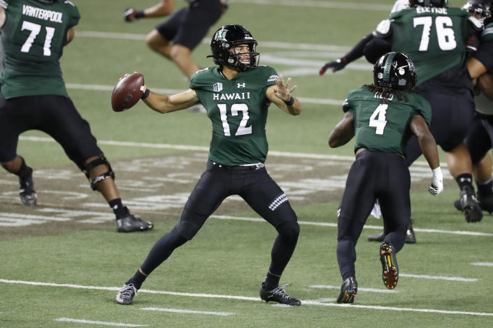 Hawaii quarterback Chevan Cordeiro (12) looks for a receiver during the first half against UNLV in an NCAA college football game Saturday, Dec. 12, 2020, in Honolulu. (AP Photo/Marco Garcia)
