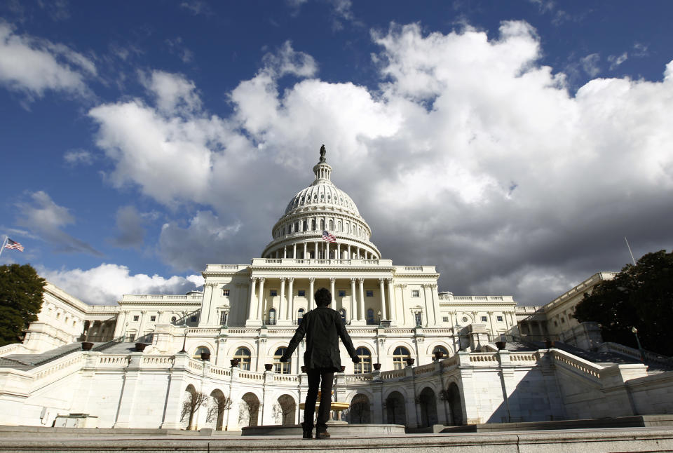 A tourist gazes up towards the dome of the U.S. Capitol in Washington January 25, 2010.  On Wednesday, U.S. President Barack Obama will deliver his first State of the Union speech in the House Chamber of the Capitol.     REUTERS/Kevin Lamarque      (UNITED STATES - Tags: POLITICS)