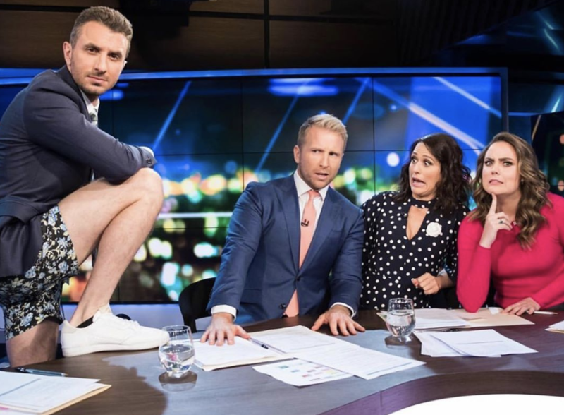 Tommy Little wears shorts and places his foot on The Project desk as his co-hosts Hamish Macdonald, Rachel Corbett and Georgie Tunny look on.