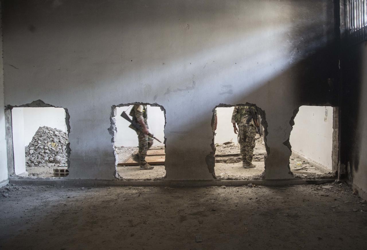 In this Oct. 20, 2017, photo, nembers of the U.S.-backed Syrian Democratic Forces (SDF) walk inside the stadium that was the site of Islamic State fighters' last stand in the city of Raqqa, Syria. Losing real estate in the Middle East will not sharply affect Islamic State militants' ability to inspire attacks against the West or burrow footholds from the Philippines to Africa, which has forced the U.S. to spread its resources thinly around the world, the nation's top counterterrorism official said Friday. (AP Photo/Asmaa Waguih)