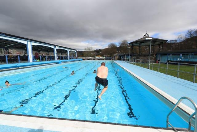 A man jumps in the pool at Hathersage outdoor swimming pool
