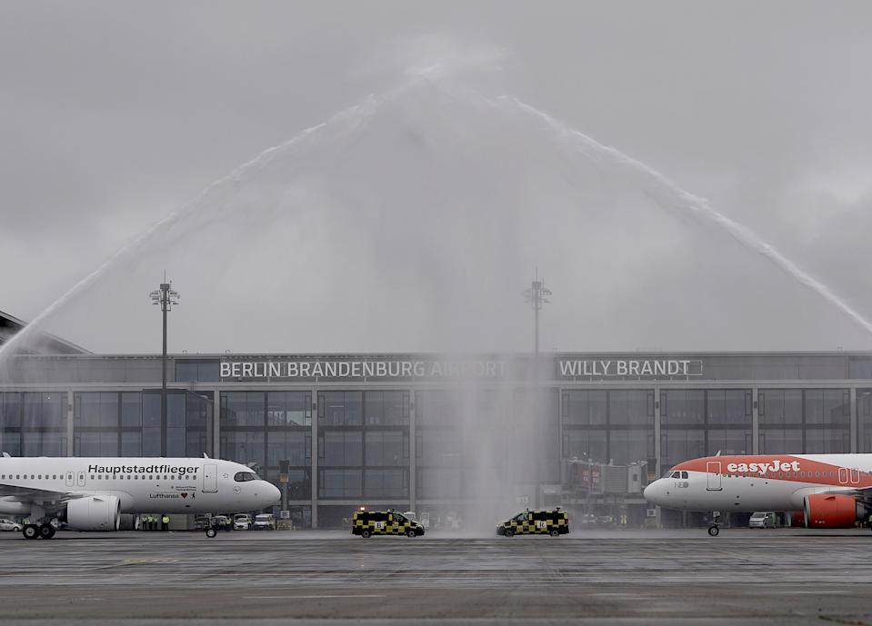 "Aircraft belonging to the airlines Lufthansa and easyJet stand after landing under a fountain of water from the airport fire brigade in front of Terminal 1 of the capital airport Berlin Brandenburg ""Willy Brandt"" (BER). Photo: Michael Kappeler/dpa via Getty Images"