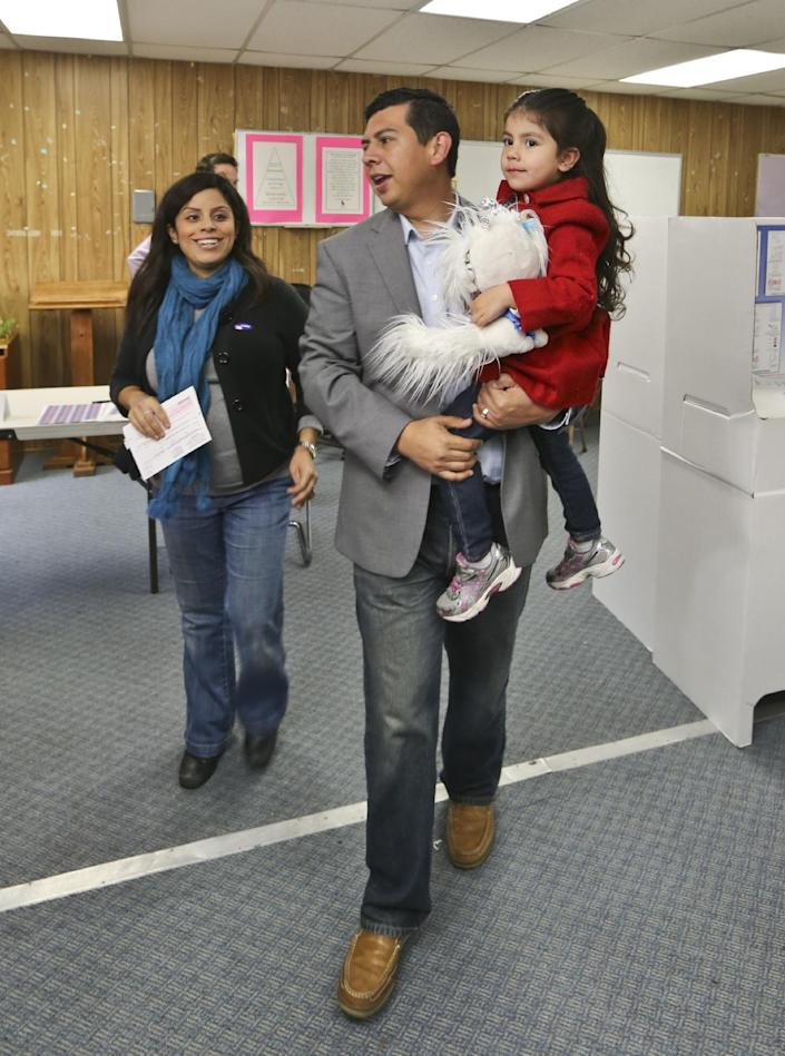 San Diego mayoral candidate David Alvarez, carries his daughter, Izel, as he and his wife, Xochitl, leave the polling location where they voted in the Logan Heights neighborhood where Alvarez grew up and still lives Tuesday, Feb. 11, 2014 in San Diego. (AP Photo/Lenny Ignelzi)