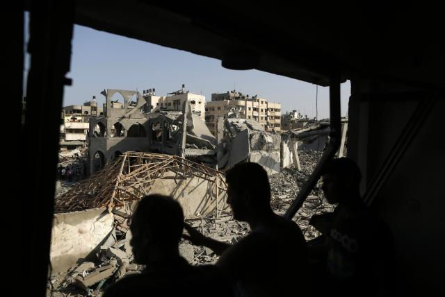 Palestinians look at the remains of a mosque, which witnesses said was hit in an Israeli air strike, in Gaza City August 2, 2014. Hamas claimed responsibility on Saturday for a deadly Gaza Strip ambush in which an Israeli army officer may have been captured, but said the incident likely preceded and therefore had not violated a U.S.- and U.N.-sponsored truce. Palestinian officials say 1,650 Gazans, most of them civilians, have been killed, including a muezzin who died in an Israeli strike on a northern mosque on Saturday. Sixty-three Israeli soldiers have been killed, and Palestinian shelling has killed three civilians in Israel. Israel launched a Gaza air and naval offensive on July 8 following a surge of cross-border rocket salvoes by Hamas and other Palestinian guerrillas, later escalating into ground incursions centred along the tunnel-riddled eastern frontier of the enclave but often pushing into residential areas. REUTERS/Suhaib Salem (GAZA - Tags: CIVIL UNREST POLITICS TPX IMAGES OF THE DAY CONFLICT)