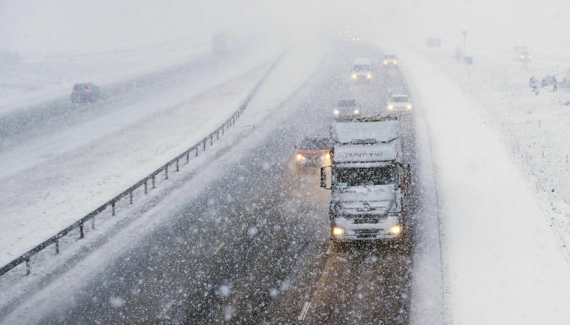 Traffic travels through snowfall on the M6 motorway near the village of Shap in Cumbria, north west England, Tuesday Jan. 29, 2019, as temperatures are expected to drop across large parts of Britain this week. Weather warnings for snow and ice have been issued by the Met Office. (Owen Humphreys/PA via AP)