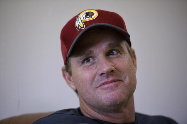 In this June 13, 2018, photo, Washington Redskins coach Jay Gruden is interviewed by The Associated Press after NFL football practice in Ashburn, Va. With Jon Gruden leaving Monday Night Football to return to the sideline after a decade away, and Jay entering his fifth season as Redskins coach, they will join the Harbaughs as the only sets of siblings to simultaneously hold jobs as NFL head coaches. (AP Photo/Nick Wass, File)