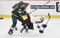 Minnesota Wild's Alex Galchenyuk, left, sends the San Jose Sharks' Brent Burns, right, to the ice in the first period of an NHL hockey game, Saturday, Feb. 15, 2020, in St. Paul, Minn. (AP Photo/Tom Olmscheid)