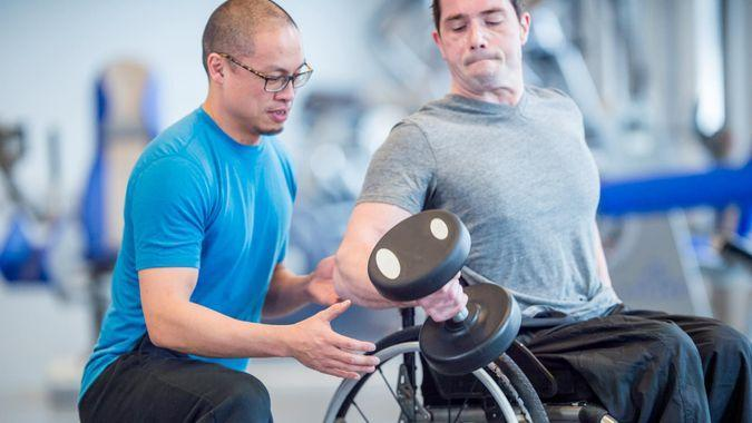 A man with a physical disability is sitting in a wheelchair and is working out at the gym with a recreational therapist