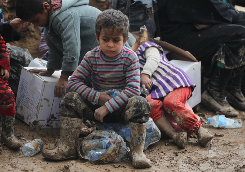 An Iraqi boy sits in mud at the Hamam al-Alil camp for displaced people on March 20, 2017 (AFP Photo/AHMAD AL-RUBAYE)