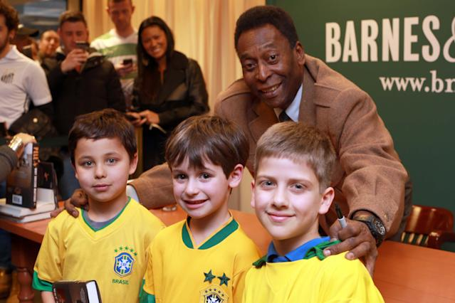 """Brazilian soccer star Pele, poses for a photo with fans, from left, Lucas LaFleur, Ethan Kaplowitzs and Lorenzo Gutierrez Baker, during an appearance at Barnes & Noble to signs copies of his book """"Why Soccer Matters"""" on Tuesday, April 1, 2014, in New York. (Photo by Luiz Ribeiro/Invision/AP)"""
