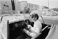 <p>Mick Jagger at the wheel of his Morgan Plus 8 Roadster, outside the Hotel Byblos in Saint-Tropez, France, May 1971. He married Bianca De Macias in the town later that month. </p>