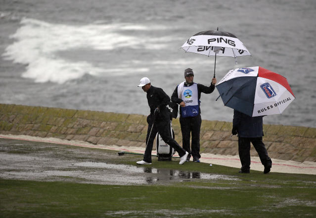 Cameron Champ walks to retrieve his mark after finding a drier spot to hit from as a rules official watches on the 18th fairway of the Pebble Beach Golf Links during the second round of the AT&T Pebble Beach Pro-Am golf tournament Friday, Feb. 8, 2019, in Pebble Beach, Calif. (AP Photo/Eric Risberg)
