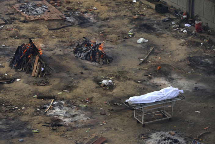 A dead body waits to be cremated as multiple funeral pyres of those who died of COVID-19 burn at a ground that has been converted into a crematorium for mass cremation of coronavirus victims, in New Delhi, India, Wednesday, April 21, 2021. Delhi has been cremating so many bodies of coronavirus victims that authorities are getting requests to start cutting down trees in city parks, as a second record surge has brought India's tattered healthcare system to its knees. (AP Photo)