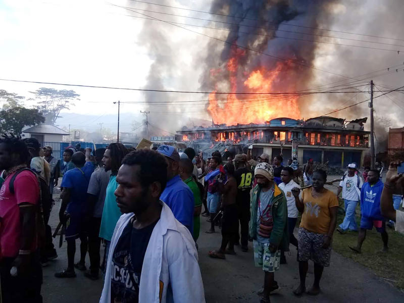 People gather as shops burn in the background during a protest in Wamena in Papua province, Indonesia, Monday, Sept 23, 2019. Hundreds of protesters in Indonesia's restive Papua province set fire to homes and other buildings Monday in a protest sparked by rumors that a teacher had insulted students, and a soldier was killed in another protest in the region, police said. (AP Photo)