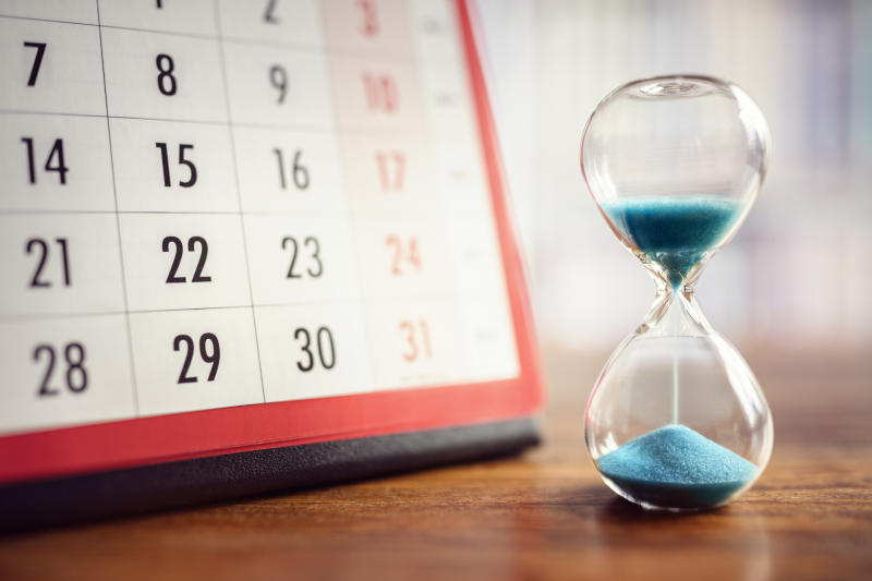 A half-empty hourglass on a table next to a calendar.
