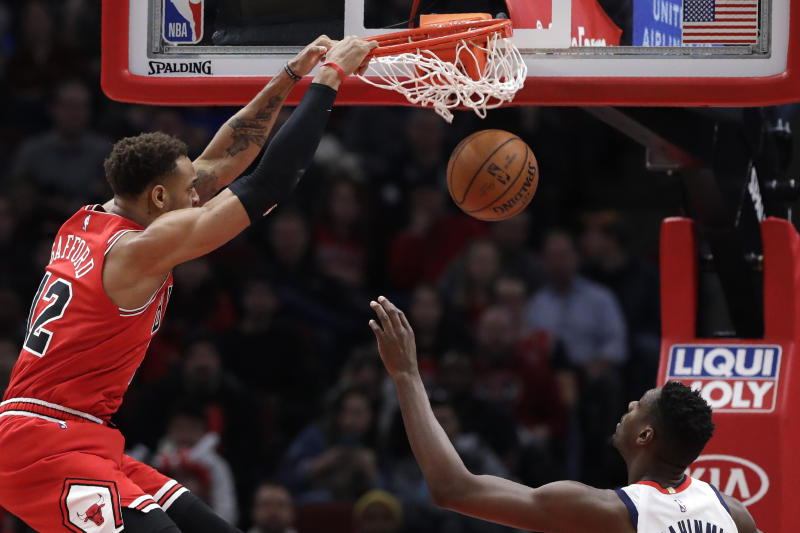 Chicago Bulls forward Daniel Gafford, left, dunks as Washington Wizards center Ian Mahinmi watches during the first half of an NBA basketball game in Chicago, Wednesday, Jan. 15, 2020. (AP Photo/Nam Y. Huh)
