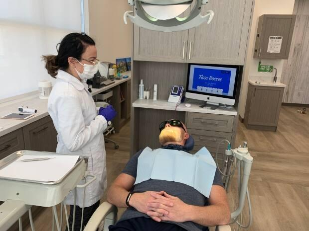 Anitka Helliker talks to her client before cleaning his teeth at Floss Bosses, a dental hygiene clinic.
