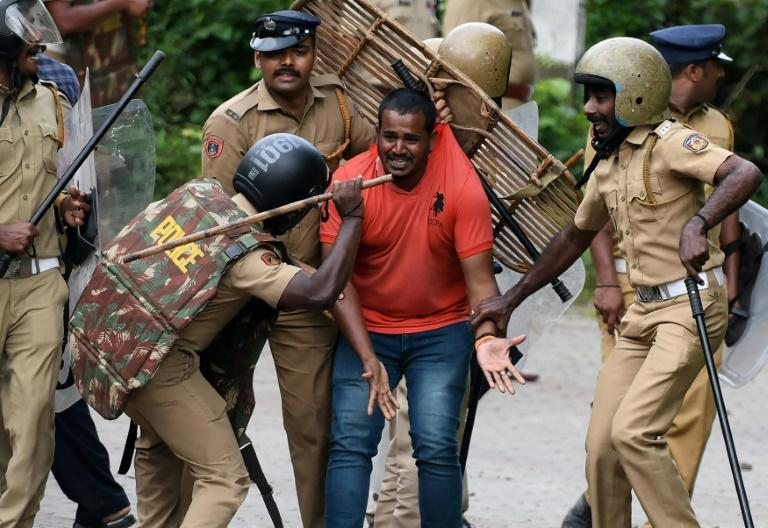 Indian police beat a Hindu activist in protests over women's acccess to a temple in Kerala