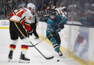 Calgary Flames' Travis Hamonic (24) battles for the puck against the San Jose Sharks' Joonas Donskoi (27) in the first period of an NHL hockey game in San Jose, Calif., Sunday, March 31, 2019. (AP Photo/Josie Lepe)