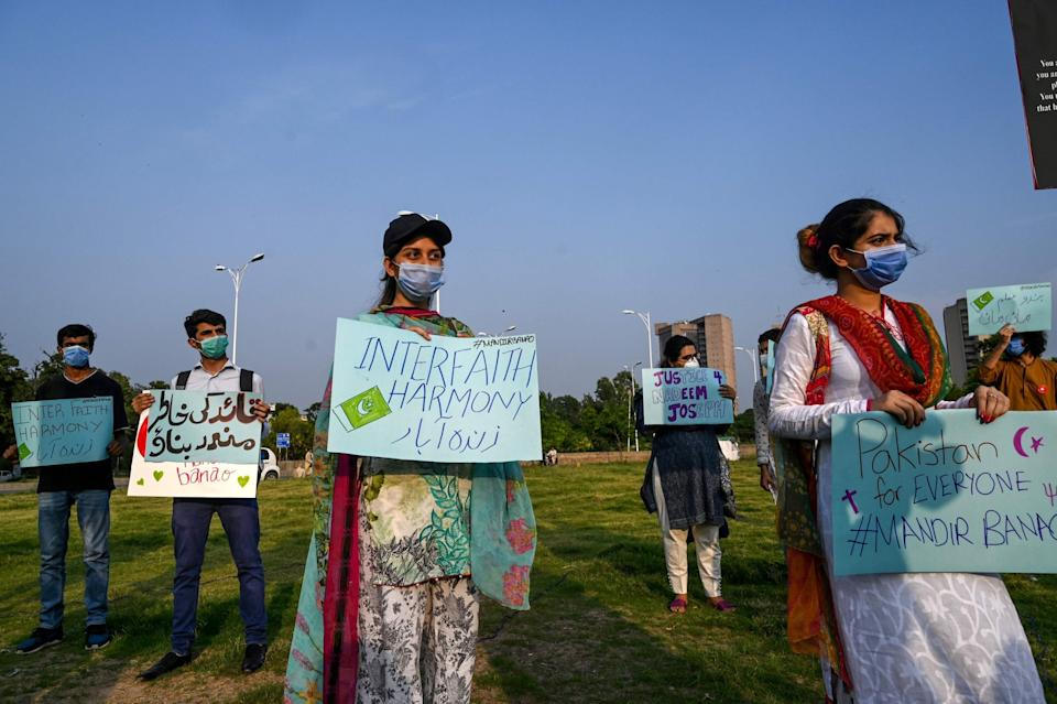 Demonstrators hold placards during a protest in support of the Islamabad temple's construction on Wednesday 8 July: AFP via Getty Images