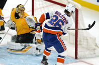 New York Islanders right wing Oliver Wahlstrom (26) hits an airborne puck with his stick as he tries to score against Boston Bruins goaltender Tuukka Rask (40) during the second period of an NHL hockey game Thursday, April 15, 2021, in Boston. (AP Photo/Elise Amendola)
