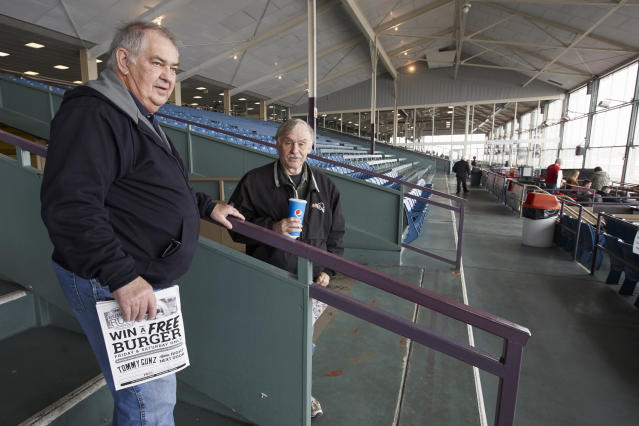 """Ron Tenski and Jerry Moritz, left, who had arrived to Fonner Park in Grand Island, Neb., for the horse races, Saturday, March 14, 2020, leave after the races were called off due to dangerous track conditions following snowfall. Fonner was one of the few sporting venues in the country open to fans Saturday, and Moritz wasn't going to let concerns over the new coronavirus stop him from going to the track. """"If we had a dozen people in the hospital here and two or three died, then I would probably back off,"""" he said. """"I feel like some people probably got it and don't even know it and are already over it."""" (AP Photo/Nati Harnik)"""