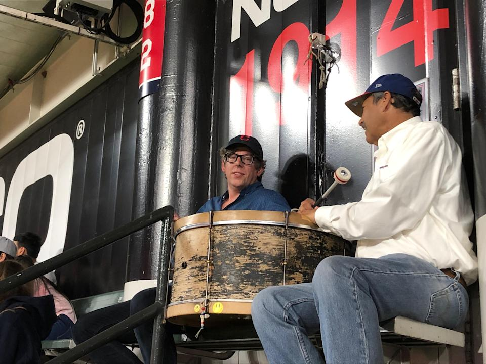 Black Keys drummer Patrick Carney (left) joined John Adams in the bleachers at a Cleveland baseball game in 2019 to beat the drums. Carney will fill in for Adams for the team's home opener on Monday.